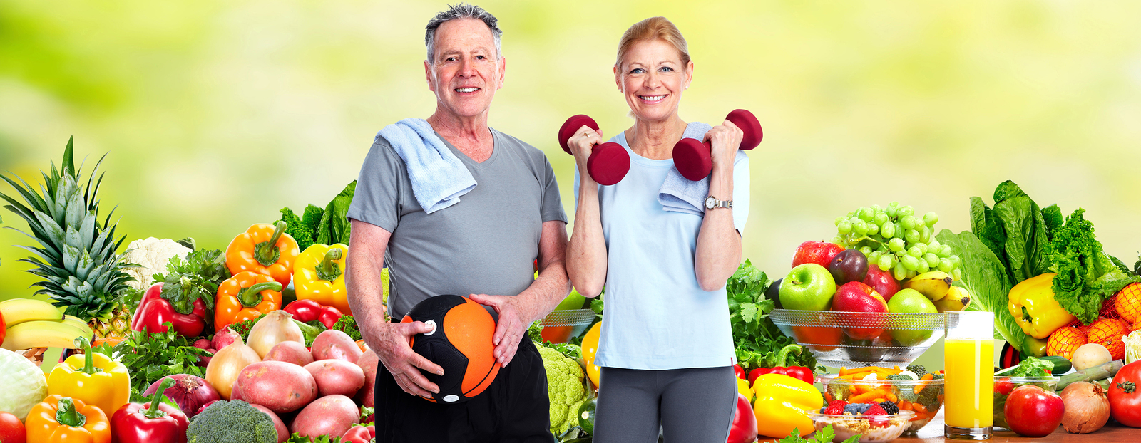 Healthy senior couple over fresh fruits and vegetables background.